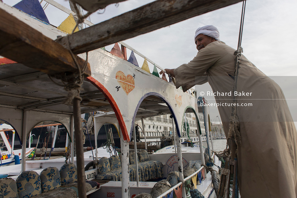The crewman of a privately-owned motorboat ferry dependent on tourist trade readies his vessel to cross the River Nile at Luxor, Nile Valley, Egypt.