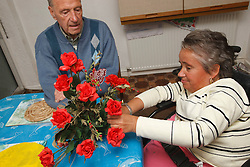 Wheelchair user with Spina Bifida arranging flowers while her father  watches