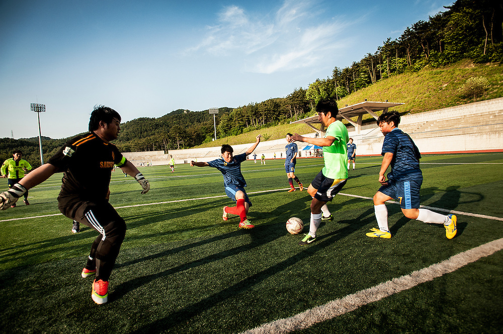 Students play soccer on a field at Silla University  in Busan, South Korea.