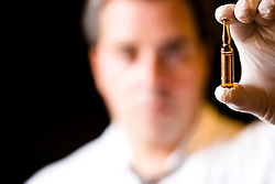 Close up of a doctor hand holding a vial between his fingers