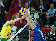 Brazil's Murilo Endres (left) attacks against France's players while volleyball match between France and Brazil during the 2014 FIVB Volleyball World Championships at Spodek in Katowice on September 20, 2014.