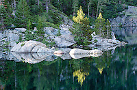 Trees and rocks reflecting in glassy Upper Sardine Lake in Tahoe National Forest, California.