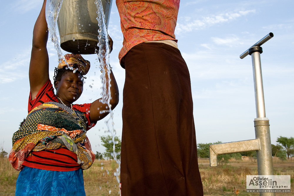 Water drips as a girl helps a woman lift a bucket of water on top of her head.