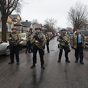 A group of Minneapolis Police officers with tear gas guns were pushed back by an angry crowd from an empty lot across the street from the Minneapolis Police Department 4th precinct headquarters, onto Newton Avenue North, where they then stood their ground, during Black Lives Matter protests on Wednesday, November 18, 2015 in Minneapolis, Minnesota. <br /> <br /> The latest round of protests erupted after activists who had been camped out in the front entrance to the precinct were cleared out earlier in the day. Protests and the encampment came in reaction to the shooting of 24-year-old Jamar Clark by Minneapolis Police on Sunday. <br /> <br /> <br /> Photo by Angela Jimenez for Minnesota Public Radio www.angelajimenezphotography.com