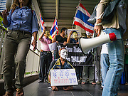 "02 JUNE 2013 - BANGKOK, THAILAND:   A legless man leads a protest march through the Bangkok skywalk system. The so called White Mask protesters are strong supporters of the Thai monarchy. About 300 people wearing the Guy Fawkes mask popularized by the movie ""V for Vendetta"" and Anonymous, the hackers' group, marched through central Bangkok Sunday demanding the resignation of Prime Minister Yingluck Shinawatra. They claim that Yingluck is acting as a puppet for her brother, former Prime Minister Thaksin Shinawatra, who was deposed by a military coup in 2006 and now lives in exile in Dubai.   PHOTO BY JACK KURTZ"