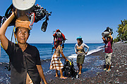 Porters of the Diving Helpers Club carrying scuba equipment for tourists in Tulamben, Bali, Indonesia. The women work for tips, which help them supplement their incomes in this remote village in northeastern Bali.
