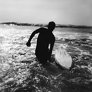 A silhouette of a surfer in the sea, with his board, UK, 1980's.