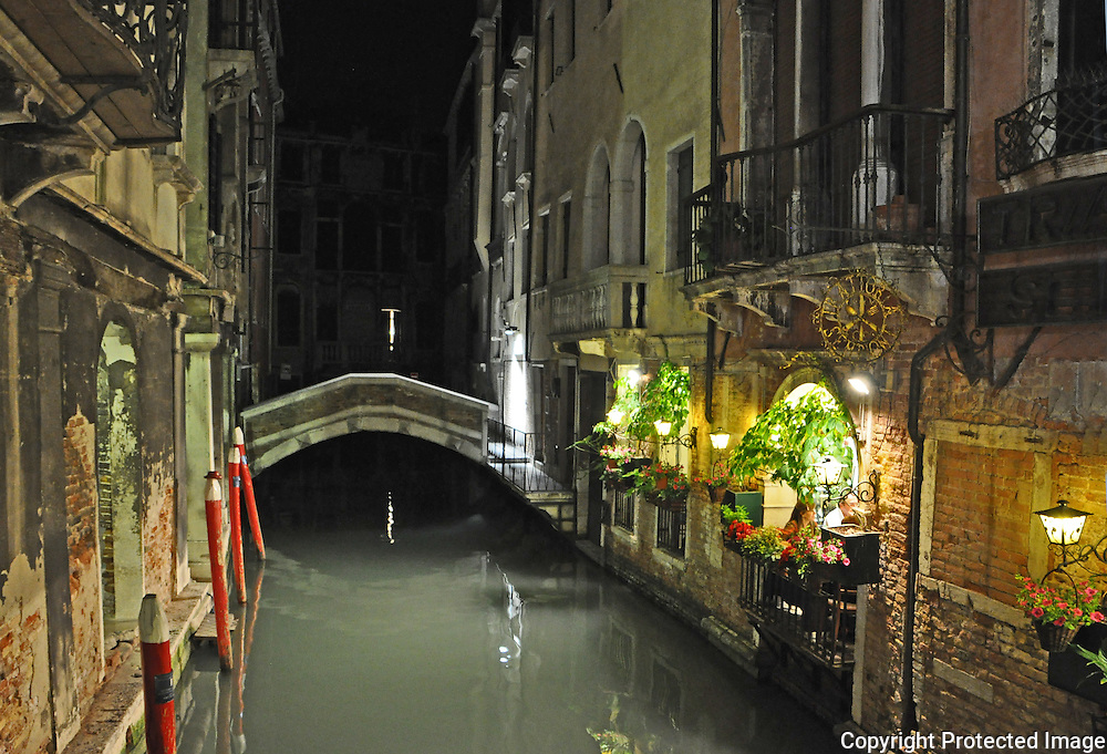 Beautifully lit canalside restaurant and bridge at night in Venice, Italy.