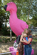 "Two women friends hug next to an extinct pink Dodo which stands in the makeshift climate change protest camp on Waterloo Millennium Green, during the week-long, country-wide protest by environmental campaigners, Extinction Rebellion, on 16th July 2019, in London, England. The five-day ""summer uprising's message is for the UK government to outlaw what protesters call 'Ecocide'."