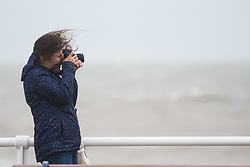 © Licensed to London News Pictures. 21/09/2018. Aberystwyth, UK. A visitor walking in Aberystwyth feels the gale force winds of Storm Bronagh, the second named storm of the UK winter.Photo credit: Keith Morris/LNP