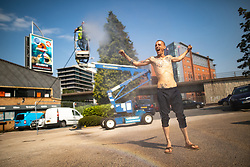 © Licensed to London News Pictures . 26/07/2018. Manchester , UK . Paint sprayer NEIL WILLIAMS (37, from Southampton) is cooled off by colleague STEVE HAMLET (43, from Southampton, on cherry picker) using a water jet spray , at a building site near Manchester City Centre . People enjoy the summer sunshine in Manchester as temperatures in the UK are forecast to break records . Photo credit : Joel Goodman/LNP