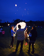 Cipriano Garrido, of Jamison, Pennsylvania (center) along with family and friends lights a lantern before releasing it into the air during the Lanterns of Hope event Saturday October 24, 2015 in Buckingham, Pennsylvania. The event was a benefit for Make A Difference Children's Foundation to help children in shelters in the United States and school children in Nigeria. (Photo by William Thomas Cain)