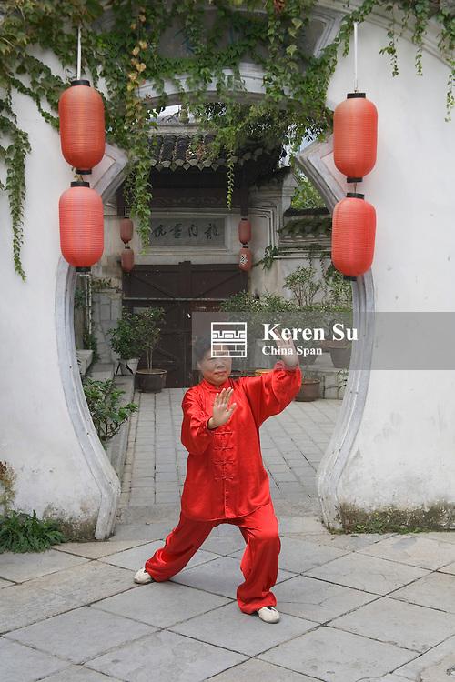 Woman playing Taichi in traditional garden, Guiyang, Guizhou, China