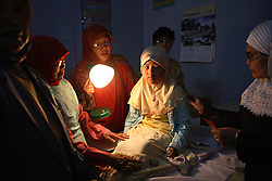 A young girl sits quietly after being circumcised in Bandung, Indonesia on April 23, 2006. The families of 248 girls were given money to have their children circumcised in a mass circumcision celebration timed to honour the Prophet Mohammed's birthday. While religion was the main reason for circumcisions, it is believed by some locals that a girl who is not circumcised would have unclean genitals after she urinates which could lead to cervical cancer. It is also believed if one prays with unclean genitals their prayer won't be heard. The practitioners used scissors to cut the hood and tip of the clitoris. The World Health Organization has deemed the ritual unnecessary and condemns such practices.