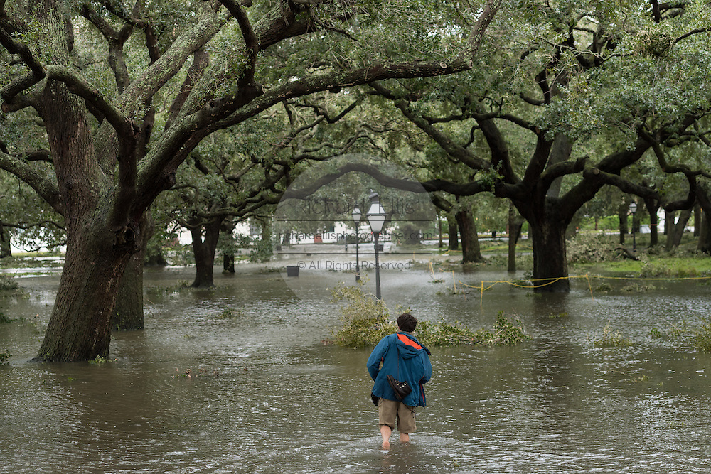 A young man wades through flood waters in White Point Gardens in historic downtown after Hurricane Matthew passed through causing flooding and light damage to the area October 8, 2016 in Charleston, South Carolina. The hurricane made landfall near Charleston as a Category 2 storm but quickly diminished as it moved north.
