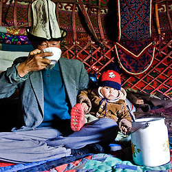 Old Kyrgyz man and grandson drinking horse milk inside his yurt. Kyrgyzstan.