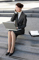 Businesswoman on outdoor Steps Using Laptop and talking on mobile