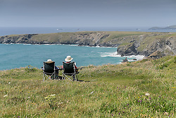 A couple relaxing and enjoying the view from the clifftop at Carnewas on the North Cornwall coast.