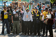 01 DECEMBER 2013 - BANGKOK, THAILAND: Anti-government protestors clench their fists before confronting riot police in Bangkok. Thousands of anti-government Thais confronted riot police at Phanitchayakan Intersection, where Rama I and Phitsanoluk Roads intersect, next to Government House (the office of the Prime Minister). Protestors threw rocks, cherry bombs, small explosives and Molotov cocktails at police who responded with waves of tear gas and chemical dispersal weapons. At least four people were killed at a university in suburban Bangkok when gangs of pro-government and anti-government demonstrators clashed. This is the most serious political violence in Thailand since 2010.    PHOTO BY JACK KURTZ