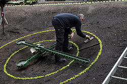 Gardener working on preparing  flower bed at the Floral Clock in Princes Street Gardens in Edinburgh, Scotland, UK