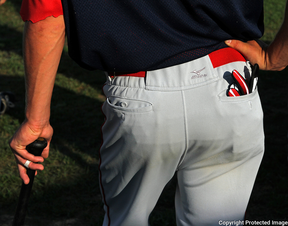 With batting glove tucked neatly into his rear pocket, a Clarinda A's player leans on his bat and waits for the game to start.  photo by David Peterson