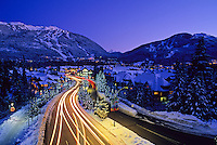 Blackcomb and Whistler mountains rise up behind Lorimer Road at twilight on a winter evening in Whistler, BC Canada. Moving cars create tracks of light along the road that leads to both mountains.