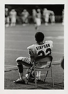 "O.J. Simpson, ""The Juice"" sits on the sideline during a game between the Buffalo Bills and the Washington Redskins in August 1970.  Photograph by Dennis Brack"