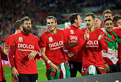CARDIFF, WALES - Tuesday, October 13, 2015: Wales' Joe Ledley, Gareth Bale and Aaron Ramsey celebrate qualifying for the finals after the 2-0 victory over Andorra during the UEFA Euro 2016 qualifying Group B match at the Cardiff City Stadium. (Pic by Barry Coombs/Propaganda)