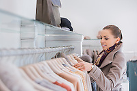 Side view of young woman choosing sweater in store