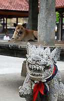Dog resting in a temple with a Balinese dog statue in the foreground.