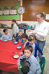 Children sitting around table eating bowls of cereal at school breakfast club,
