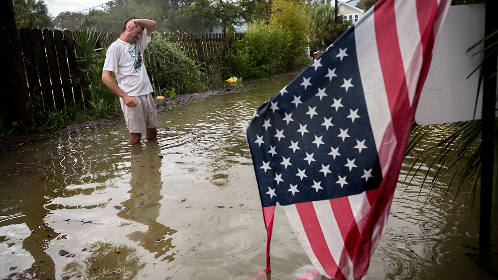 Tybee Island resident Joe Murphy wipes the sweat off his face while standing in knee deep water outside his house, Monday, Sept., 11, 2017, on Tybee Island, Ga. (AP Photo/Stephen B. Morton)