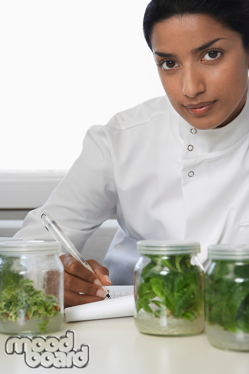 Female lab worker with glass jars with plant material recording observations