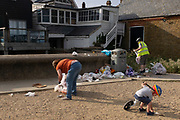 The morning after Saturday night crowds of young peoples' nightlife beach parties, their litter and rubbish from the night before stretches across the coastal paths and shingle, a child looks for feathers as local volunteers pick up and bag up piles of litter along the sea wall, on 19th July 2020, in Whitstable, Kent, England.  The volunteers and a council cleaner come every morning to clean-up the mess left by others which, they say, has got worse during the Coronavirus pandemic lockdown and now, the slow easing of health guidelines.