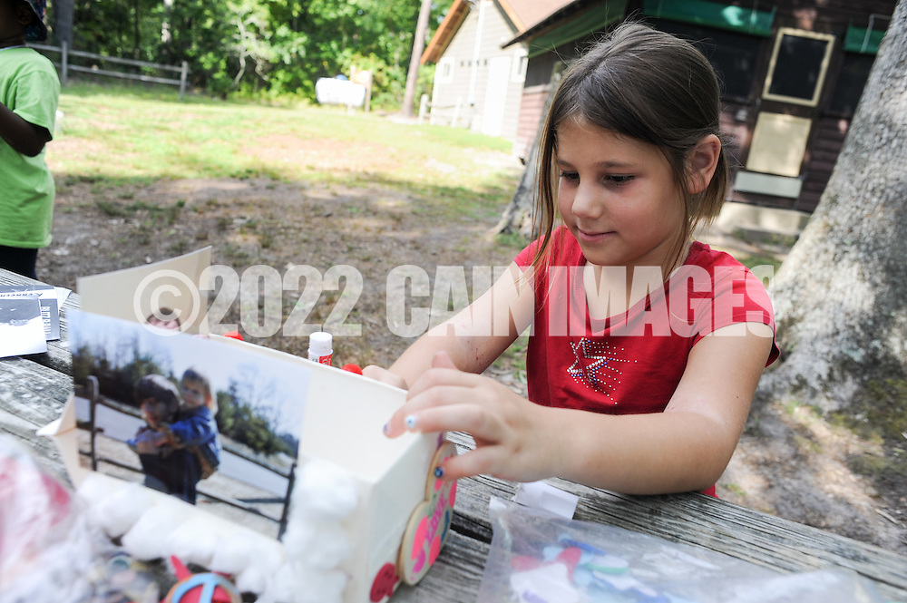 Evie Malaeve works on a boat in remembrance of her brother Josh at Camp Firefly Saturday August 27, 2016 in Medford, New Jersey. The children attending the camp have all recently experienced the death of someone close to them, and are participating to help develop positive coping strategies for their feelings of grief.  (Photo by William Thomas Cain)