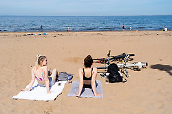 Portobello, Scotland, UK. 20 May 2020. Hot sunny weather brought out large crowds to Portobello beach today. Lockdown discipline seems to be a thing of the past with families and friends hitting the sand. A heavier than normal police presence had little visible effect since the public returned to the sand after the police walked away.  Iain Masterton/Alamy Live News