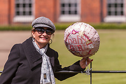 © Licensed to London News Pictures. 03/05/2015. London, UK. A tourist from Italy poses with a balloon tied to a railing outside the Golden Gates at Kensington Palace for the new daughter of the Duke and Duchess of Cambridge who was born the previous day. Photo credit : Stephen Chung/LNP