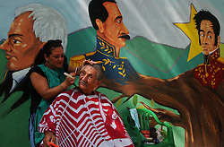 "Eileen Marquez, a member of the Bolivarian Circle, cuts the hair of Franklin Moreno in a plaza in downtown Caracas that is referred to as ""The Plaza of the Revolution"".  The two are ""Chavistas"", the name given to supporters of President Hugo Chavez. ""This is the begining of the changes that the country has always wanted"" says Moreno.  In the background are images of famous figures in Venezuelan history, Francisco Miranda(left), Ezekiel Zamoro(middle) and Simon Bolivar."