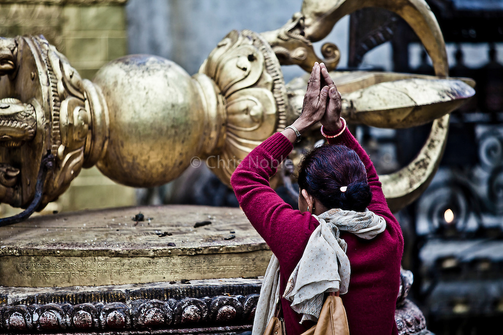"A woman bows and prays before an enormous ""Dorje,"" a symbol of the lightning bolt of enlightenment, which greets visitors to Swayambunath, one of the oldest and most holy religious sites in Kathmandu."