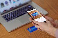 Woman with iPhone X in her hand scanning a credit card with Apple Pay, Apple Wallet electronic payment app