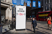With a further 184 reported UK Covid deaths in the last 24 hrs, a total now of 43,414, an elderly man passes through Oxford Circus where a post advises Londoners to observe the correct two metre social distances, during the Covid pandemnic lockdown, now easing after three months of the Stay At Home policy but now being relaxed as the shops re-open, on 26th June 2020, in London, England. Government restrictions on the 2 metre rule is to be realxed on 4th July and replaced with 'one metre plus' in the hope it stimulates the struggling UK economy.