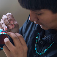 Skler Yazzie hand stitches a design on a children's shoe at the Anna & Family Creations office in Gallup Tuesday.