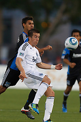 July 20, 2011; Santa Clara, CA, USA;  Vancouver Whitecaps midfielder Jeb Brovsky (12) wins a loose ball in front of San Jose Earthquakes forward Chris Wondolowski (back) during the first half at Buck Shaw Stadium.