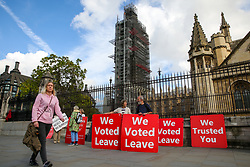 © Licensed to London News Pictures. 01/10/2019. London, UK. A woman walks past pro-Brexit protesters as they demonstrate outside Houses of Parliament with thirty days remaining until Brexit Day. It has been reported that Prime Minster Boris Johnson has asked EU to rule out a further Brexit extension as part of a proposed new deal for the UK's departure from the bloc.Photo credit: Dinendra Haria/LNP