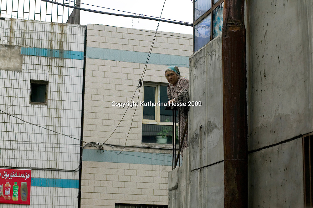 URUMQI, JULY-15 : an elderly Uighur woman looks from her balcony in Urumqi's Xiangyang Po  district, a poor quarter of the city dominated by Uighurs, Turkic-speaking Muslims who have often had an uneasy relationship with China's Han majority. Uighurs are the largest ethnic group in Xinjiang, but in Urumqi, Han make up more than 70 percent of the 2.3 million residents.<br /> Many Han Chinese were killed in Xiangyang Po during the protests in early July 2009.