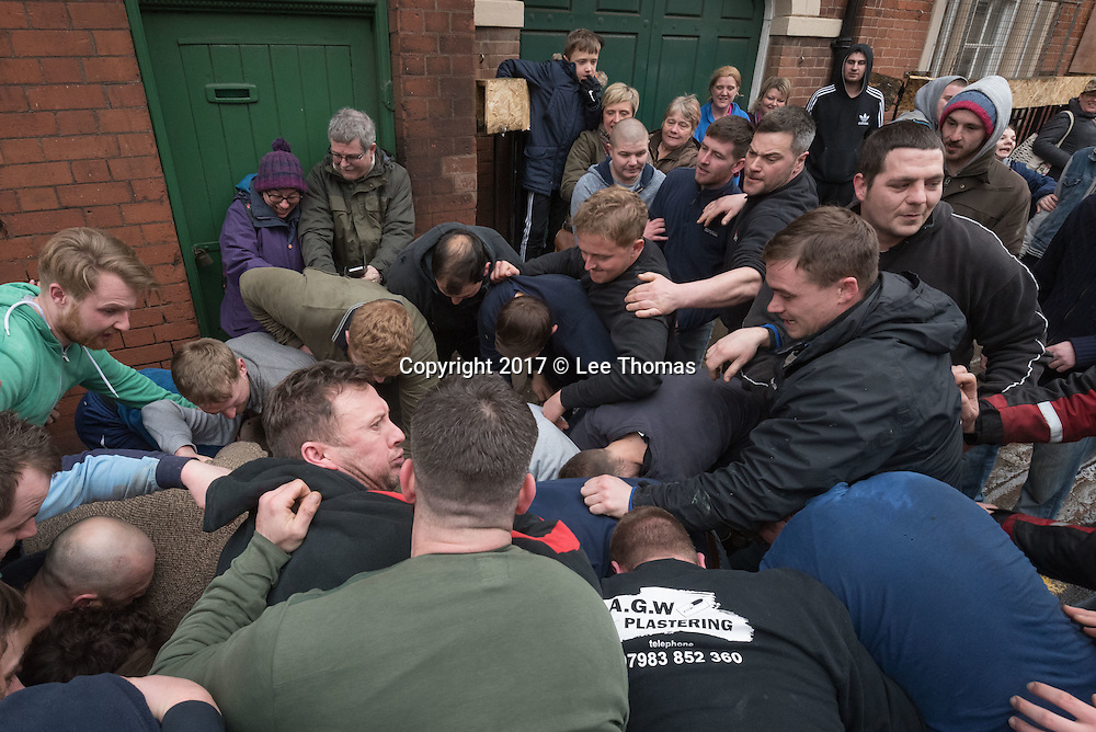 "Atherstone, Warwickshire, UK. 28th February 2017. Pictured:  / Hundreds of people of all ages flood into the Warwickshire town of Atherstone to either participate or watch the infamous Atherstone Ball Game. The event is being held for the 818th time opening when this year's celebrity, Eastenders star Annette Badland, throws the ball into the crowd of people. The Atherstone Ball Game is an ancient Shrove Tuesday tradition in which the people of this rural North Warwickshire town awaken and literally brawl over a large ball up and down the town's small ancient streets. Shops are boarded up, local schools are closed and towns people of Atherstone gather in the main street at 3pm with only one rule in mind, the ball cannot be taken outside the town. Anything and everything else goes. The winner in this no holds barred contest is the person holding onto the ball at 5pm. This traditional Shrove Tuesday Ball Game has been held annually since the early 12th Century and is one of Atherstone's claims to fame. The origin of the game, in the reign of King John, is thought to have been a ""Match of Gold that was played between the Warwickshire Lads and the Leicestershire Lads on Shrove Tuesday"".  // Lee Thomas, Tel. 07784142973. Email: leepthomas@gmail.com  www.leept.co.uk (0000635435)"