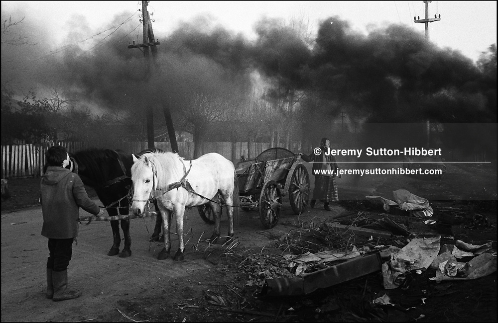 SMOKE BILLOWS FROM A NEARBY METAL FURNACE PAST BULACHE MIHAI, IN FOREGROUND AND HIS SISTER VETA. SINTESTI, ROMANIA. JANUARY 1994..©JEREMY SUTTON-HIBBERT 2000..TEL. +44-141-649-2912..TEL. +44-7831-138817.