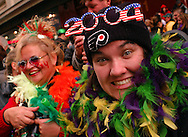 PHILADELPHIA - JANUARY 1: Dianne Stinger (L), of Merchantville, New Jersey, and Casey Richardson (R), of Franklinville, New Jersey watch the 103rd New Year's Day Mummer's Parade January 1, 2004 in Philadelphia, Pennsylvania. The day long parade features four divisions which are Comics, Fancy Clubs, Fancy Brigades, and String Bands. The clubs develop a theme, create costumes, build sets and props, and coreograph musical and dance numbers while competing for $386,000 in prizes. (Photo by William Thomas Cain/Getty Images)