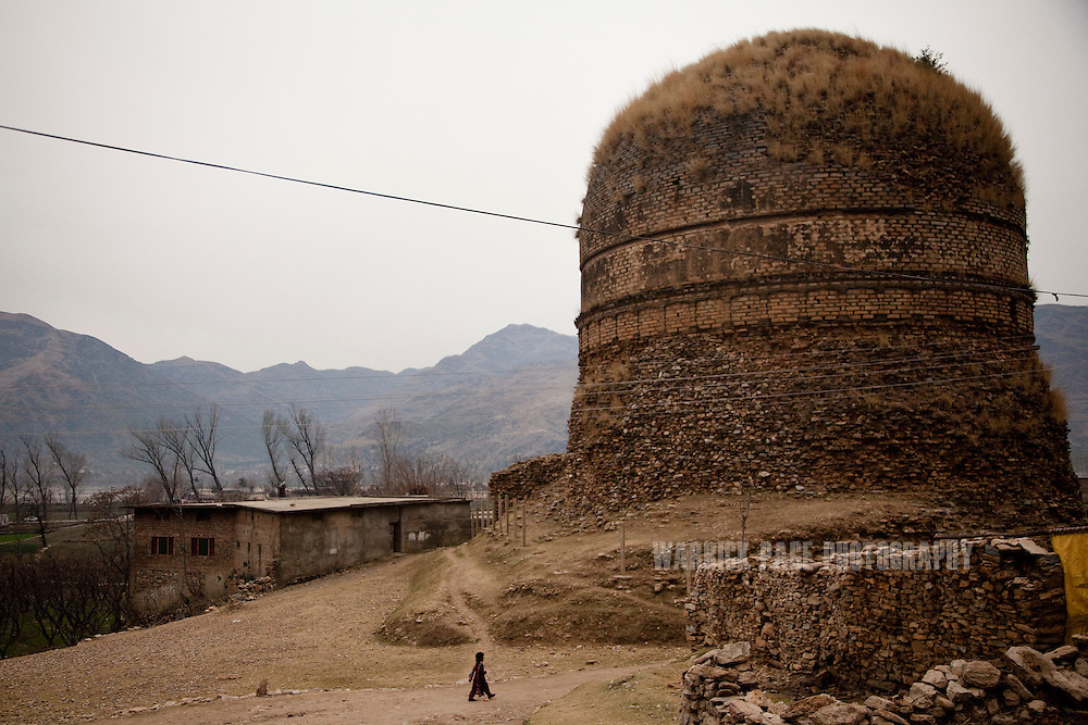 A child walks past the Shingardar Stupa in the Swat Valley, on February 11, 2011, in Gumbatuna, Pakistan. The Kingdom of Gandhara lasted from early 1st millennium BC to the 11th century AD, and was located in northern Pakistan and eastern Afghanistan. (Photo by Warrick Page)