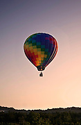Colorful hot air balloon rises up in the sky.